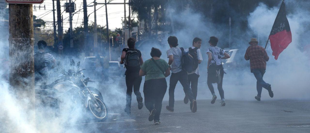 Flucht vor Tränengas. Kurz vor Anpfiff der Partie Brasilien : Kroatien lösten Polizisten gewaltsam eine Demonstration auf. Foto: Philippe Desmantez / AFP