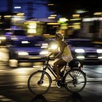 Frau auf Fahrrad vor Autos