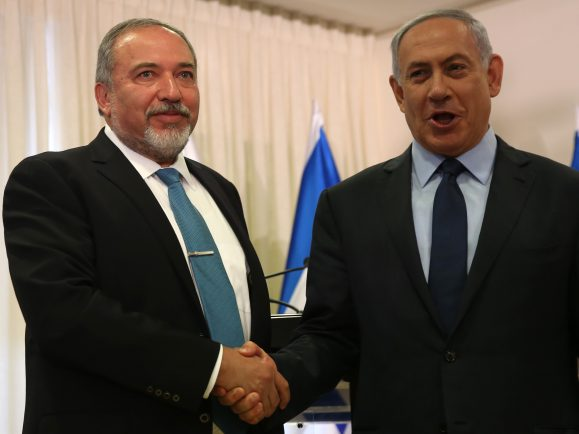 Israeli Prime Minister Benjamin Netanyahu (R) and Avigdor Lieberman (L), the head of hardline nationalist party Yisrael Beitenu, are seen during a ceremony in which they signed a coalition agreement on May 25, 2016 at the Knesset, the Israeli parliament in Jerusalem. A deal has been reached to bring far-right former foreign minister Avigdor Lieberman and his Yisrael Beitenu party into Israel's governing coalition pushing it further to the right. Prime Minister Benjamin Netanyahu will expand  his coalition to 66 lawmakers and make Lieberman defence minister. / AFP PHOTO / MENAHEM KAHANA