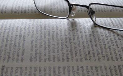 In Zukunft bekommen Menschen mit Sehproblemen ihre Brille (ab sechs Dioptrien) von der Krankenkasse bezahlt. Foto: Buchseite mit Brille | CC BY 2.0 | friek_magazine / flickr.com
