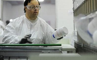 Ein Mensch mit Behinderung bei der Arbeit in einer Chemiefabrik. Foto: Sebastien Bozon | AFP