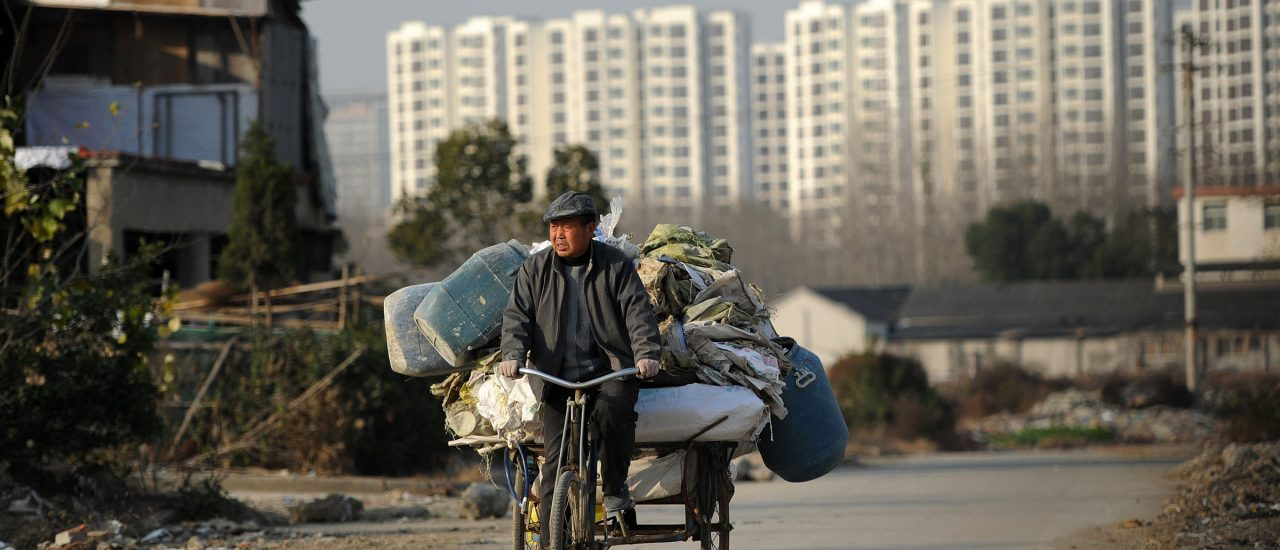 Ein Abfallsammler fährt Fahrrad. Hinter ihm die Hochhäuser der chinesischen Stadt Hefei. Foto: STR | AFP
