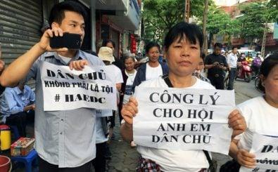 """Ein Demonstrant hält die Losung """"Demokratie ist kein Verbrechen"""" vor dem Gericht in Hanoi hoch. Foto: Jenny Vaughan / AFP"""