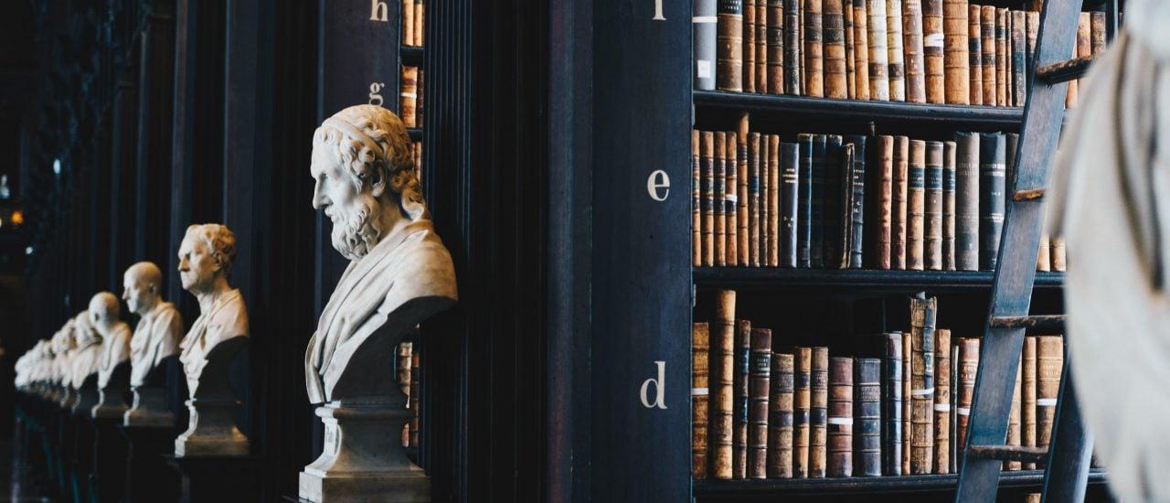 Bei den Büchern von Felix Meiner Verlag zählt nicht nur der Inhalt, auch die Form spiegelt die Philosophie wider. Foto: Bust, statue, man and library | Unsplash | Giammarco Boscaro