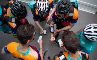 Deliveroo-Mitarbeiter warten darauf, dass die App ihnen den nächsten Arbeitsschritt anzeigt. Foto: Gerard Julien | AFP