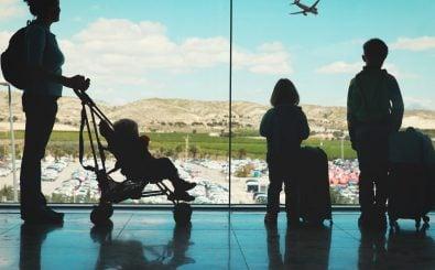 Eine Mutter steht mit Kindern und Gepäck am Flughafen. Foto: Nadya Eugene / shutterstock.com