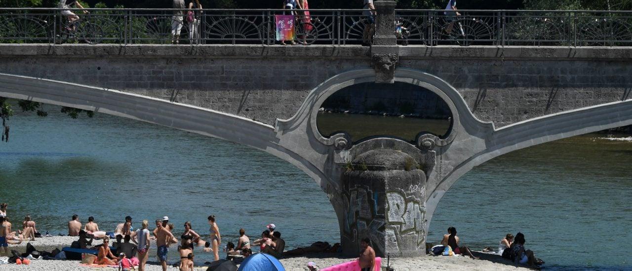 Um der Hitze zu entfliehen, kommen viele MünchnerInnen ans Isarufer. Foto: Christof Stache | AFP