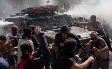 Ein Panzerwagen der chilenischen Polizei fährt in Demonstranten. Das Foto wurde am 20. Oktober 2019 in Santiago geschossen. Foto: Claudio Reyes | AFP