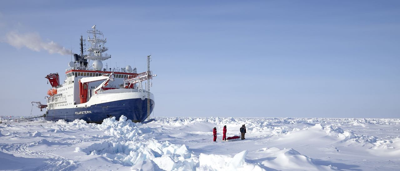Polarstern drifting in the arctic ice with scientists in the front on the right side. Foto: Michael Gutsche / Alfred-Wegener-Institut