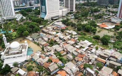 Die überfluteten Straßen in einem armen Wohnbezirk im Herzen der Stadt Jakarta. Daneben moderne Hochhäuser.