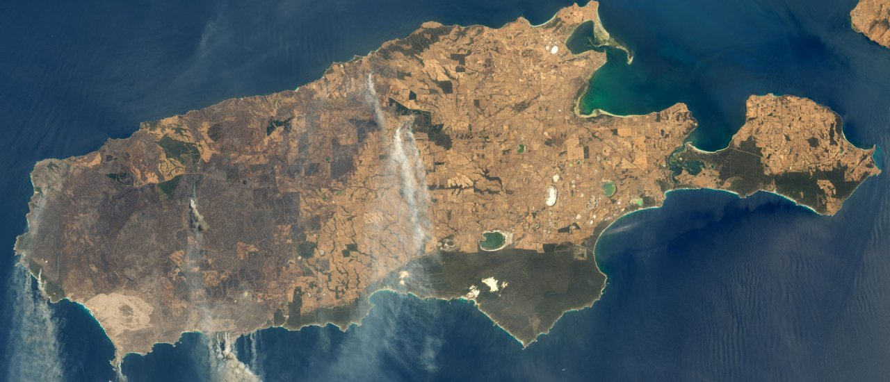 """This January 9, 2020, satellite image obtained from NASA Earth Observatory shows smoke from wildfires on Kangaroo Island, Australia. – On Kangaroo Island off South Australia, the largest town was cut off as firefighters battled dangerous infernos, forcing some residents to flee to the local jetty. (Photo by HO / NASA Earth Observatory / AFP) / RESTRICTED TO EDITORIAL USE – MANDATORY CREDIT """"AFP PHOTO / NASA Earth Observatory"""" – NO MARKETING – NO ADVERTISING CAMPAIGNS – DISTRIBUTED AS A SERVICE TO CLIENTS"""