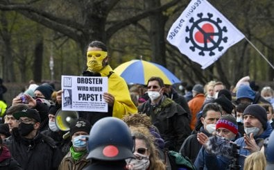 """Police observe a masked protestor taking part in a demonstration holding a poster with an image of German virologist Christian Drosden reading, """"Drosden will be the new Pope"""" in Berlin on April, 13, 2021, as anti lockdown critics and so-called 'Querdenker' gathered outside the German parliament on Tuesday, amid the Covid-19, corona pandemic. (Photo by John MACDOUGALL / AFP)"""